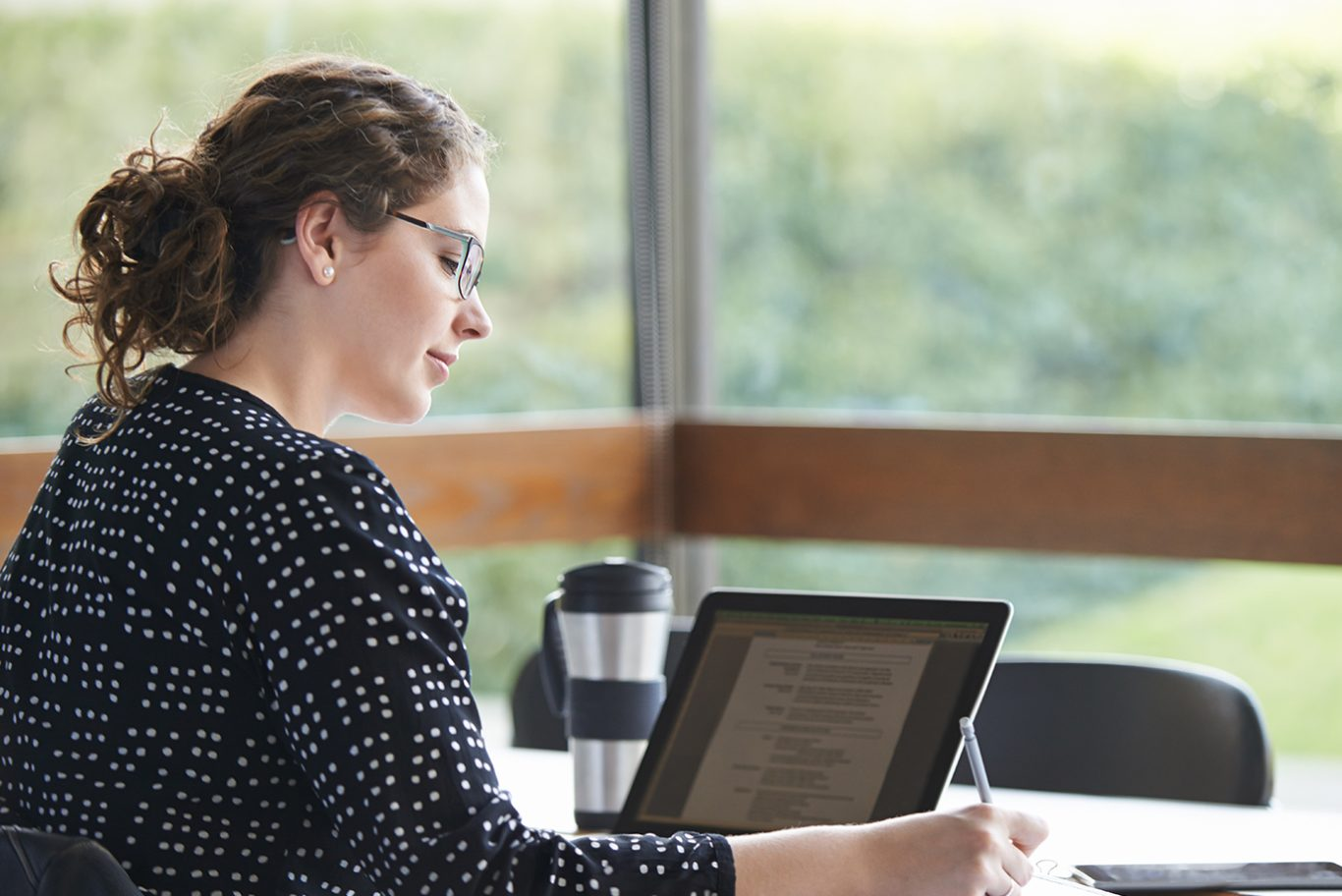 Woman sat at her desk, reading training documents and making notes.